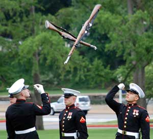 The Marine Silent Drill Team tosses rifles at each other
